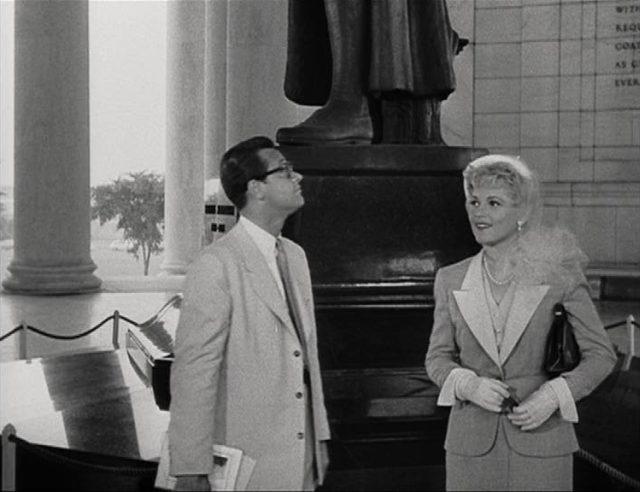 Paul Verrall und Billie Dawn auf ihrer Exkursion in Washington, hinter ihnen zeichnen sich eine Statue und Säulen ab.