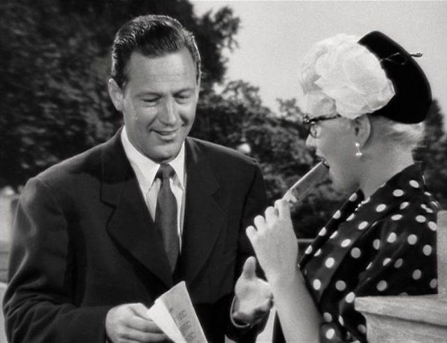 Nahaufnahme von Verrall und Dawn; er erklärt etwas lächelnd, sie hört interessiert zu und schleckt ein Eis am Stiel.