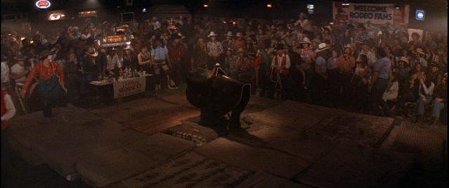 Blick auf eine unbemannte Bullriding-Maschine bei einem Rodeowettbewerb; die Fläche ist umgeben von mehreren Zuschauerreihen.