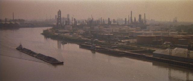 Blick auf einen Fluss, im Hintergrund stehen industrielle Anlagen.