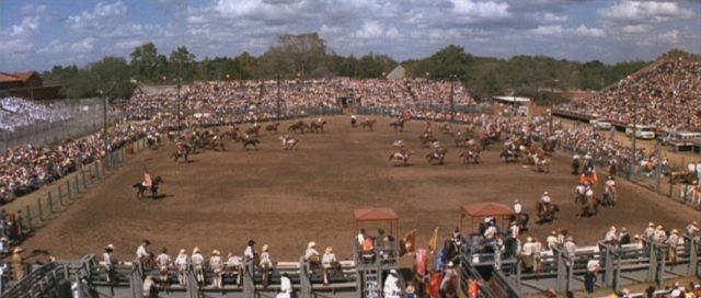 Blick auf eine Massenveranstaltung, bei der sich vor viel Publikum gerade etliche Reiter durch die Arena bewegen.