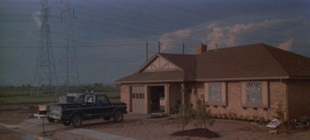 Einstöckiges Einfamilienhaus am Ortsrand; in der Einfahrt parkt ein Pick-up, im Hintergrund stehen zwei riesige Strommasten.