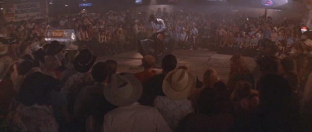 Um die Bullriding-Fläche, auf der sich jemand an der Maschine versucht, stehen zu allen Seiten mehrere Reihen Zuschauer.