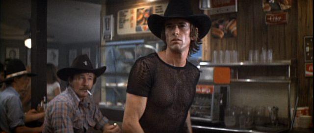 Scott Glenn erhebt sich als Wes an der Bar, gekleidet in dunklem Netzhemd und mit schwarzem Cowboyhut.