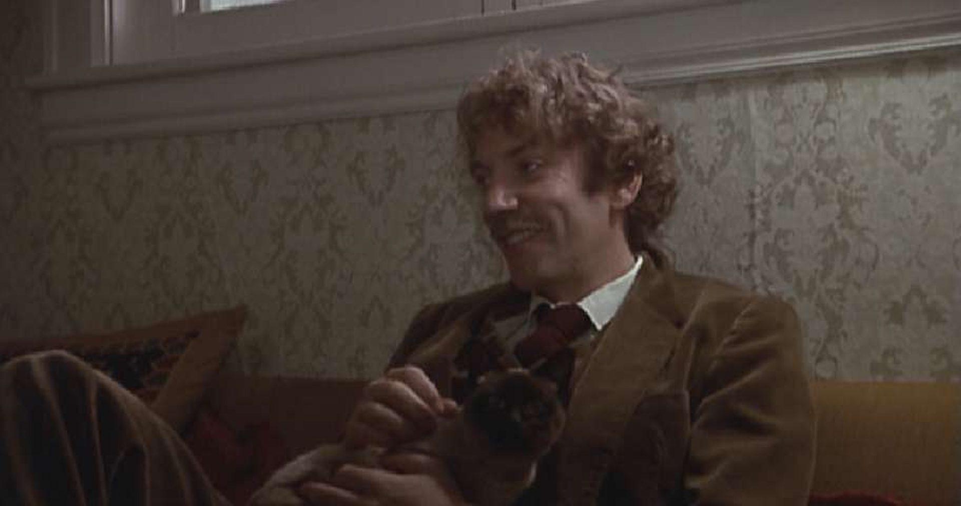 Donald Sutherland in akademischem Outfit als Dozent, der grinsend an einer Wand lehnt.