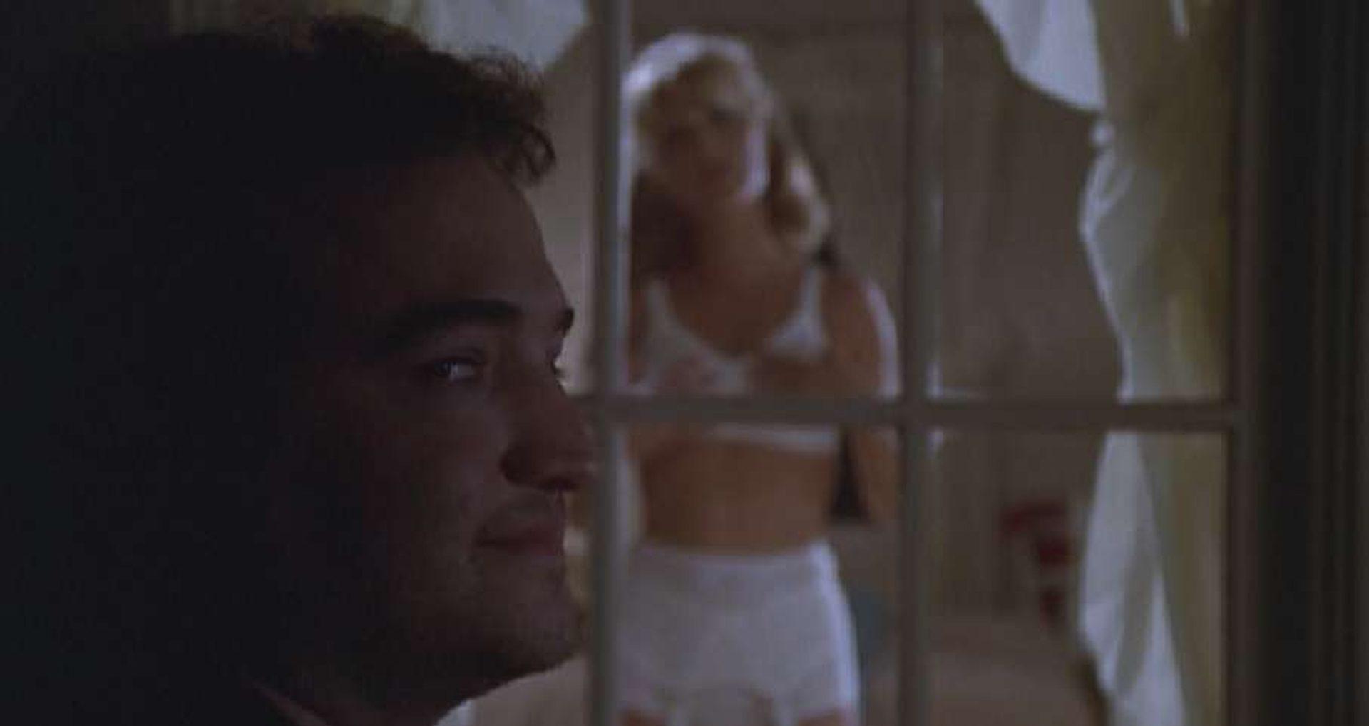 Im Vordergrund ein grinsender John Belushi, im Hintergrund an einem Fenster steht eine junge Frau in Unterwäsche.