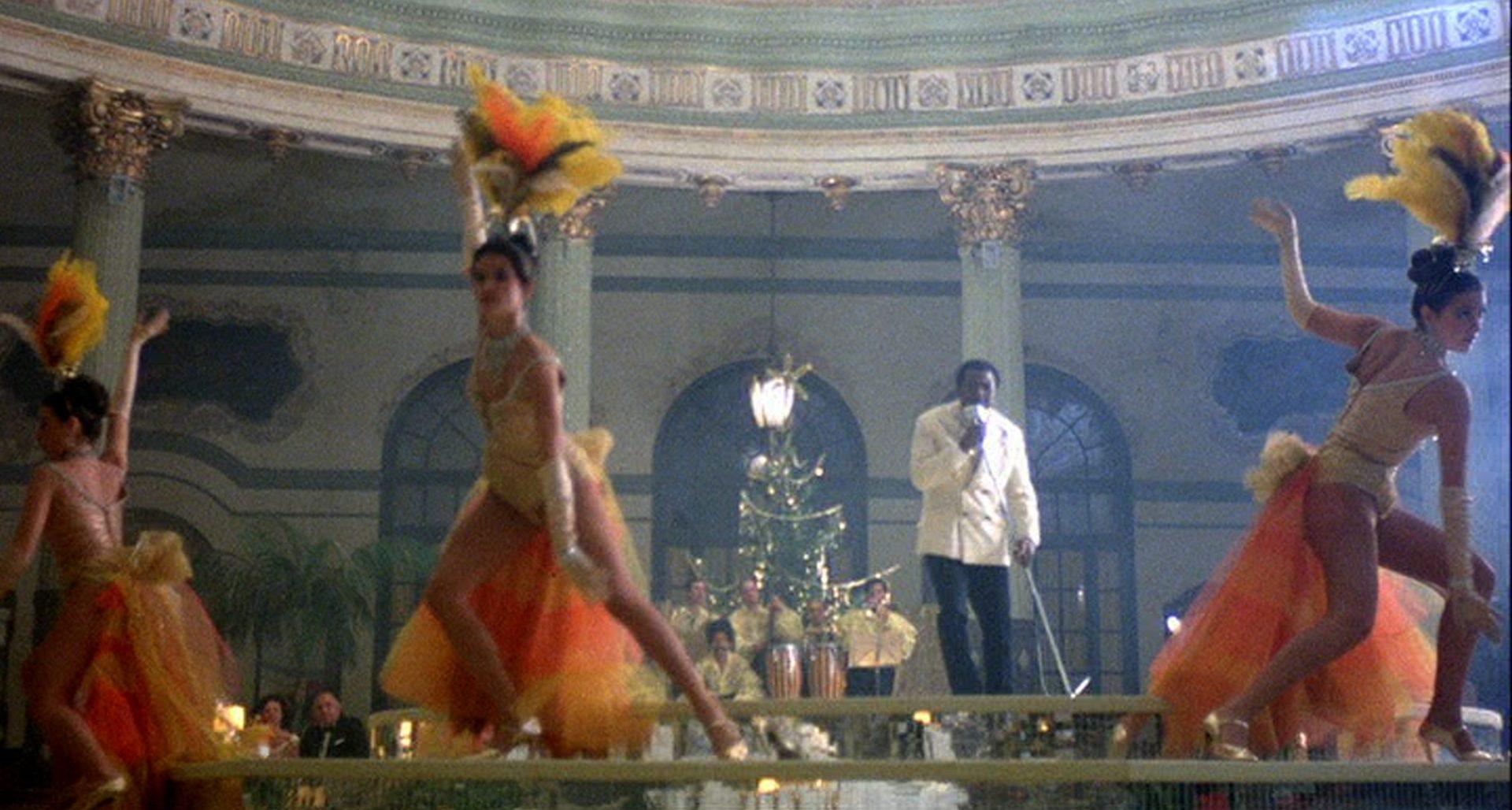 Drei Tänzerinnen und ein Entertainer beim Auftritt in einem Hotel.