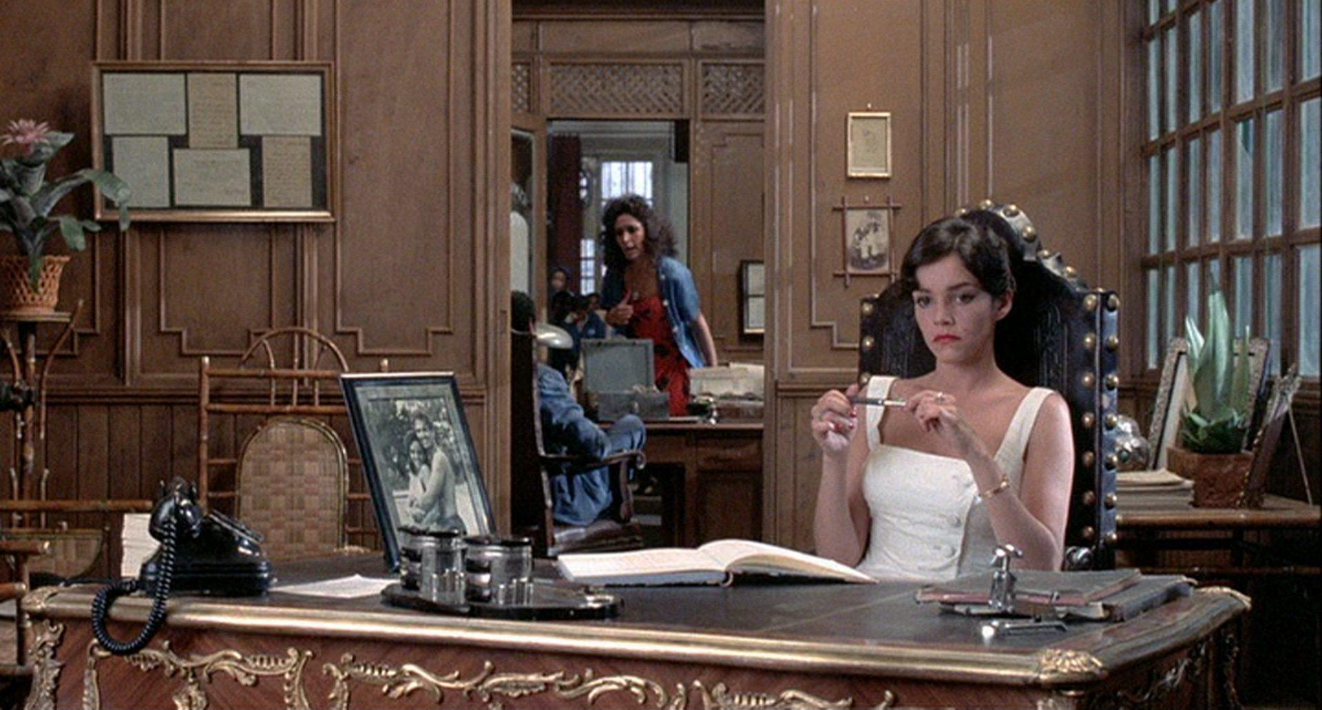 Brooke Adams als kubanische Geschäftsfrau an ihrem aufwendig verzierten Schreibtisch.