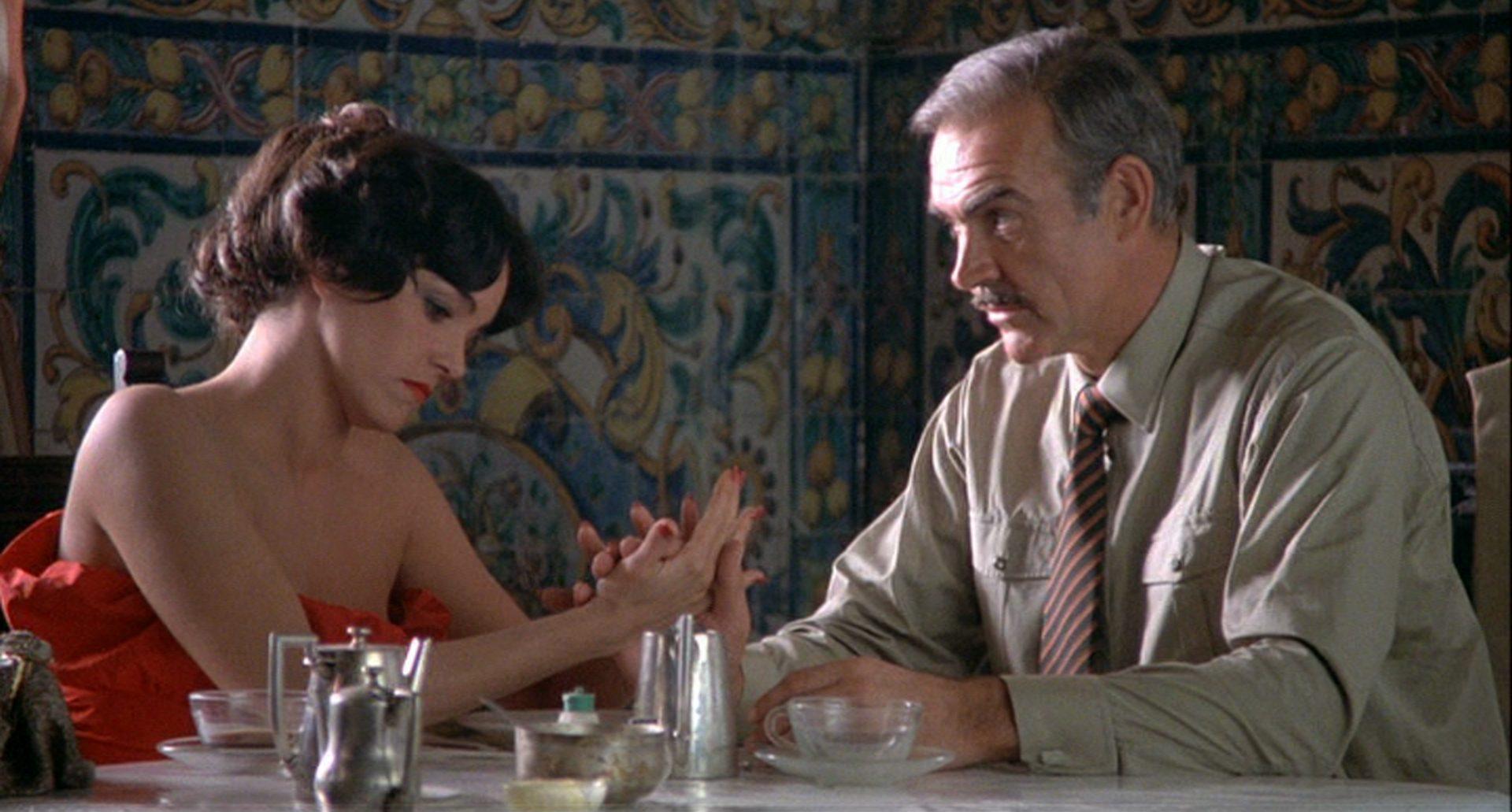 Nahaufnahme von Brooke Adams und Sean Connery an einem Restauranttisch.