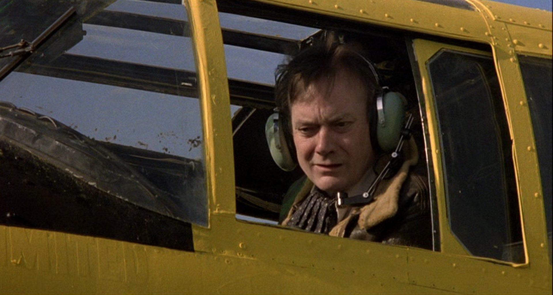 Nahaufnahme von Denholm Elliott im Cockpit.