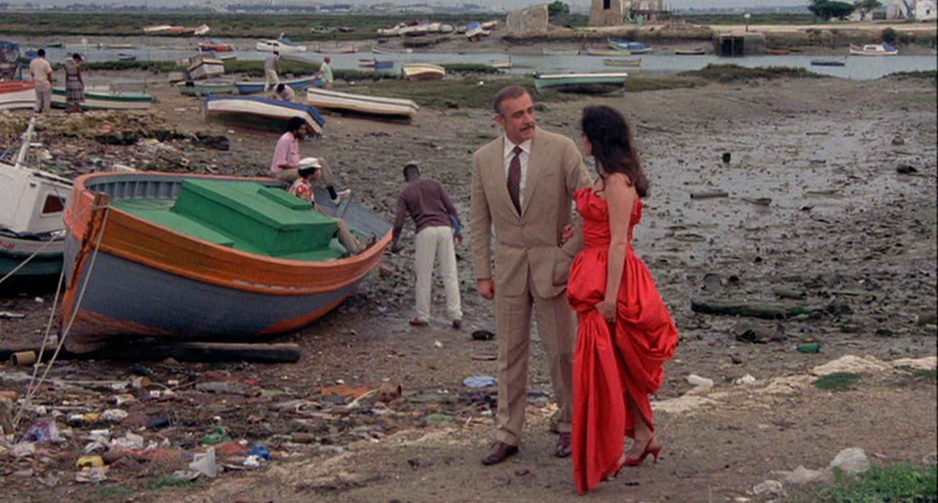 Connery in matschiger Umgebung mit kleinen Booten im Hintergrund.