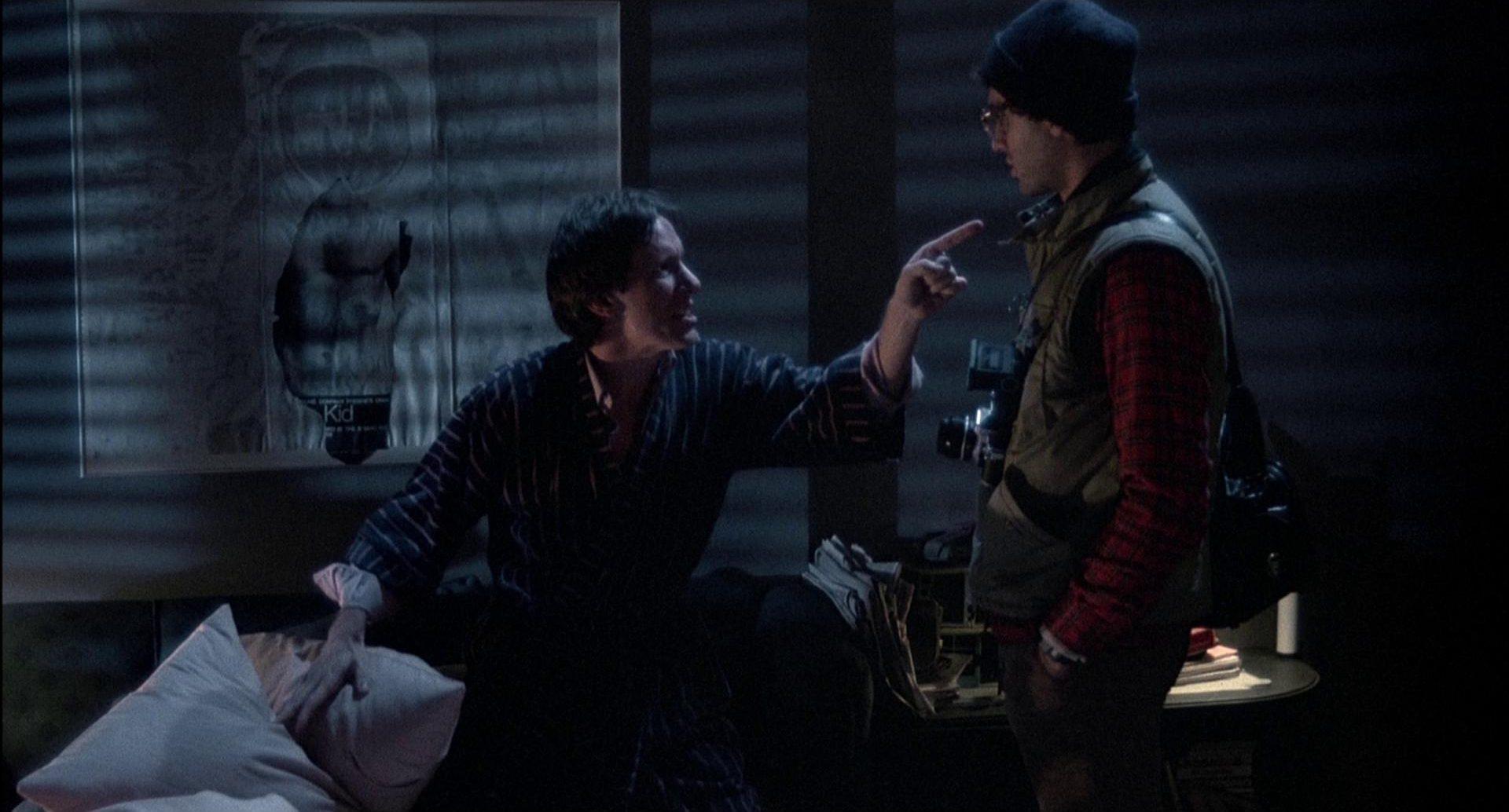 Verärgerter Renn in dunklem Zimmer im Gespräch mit seinem Techniker.