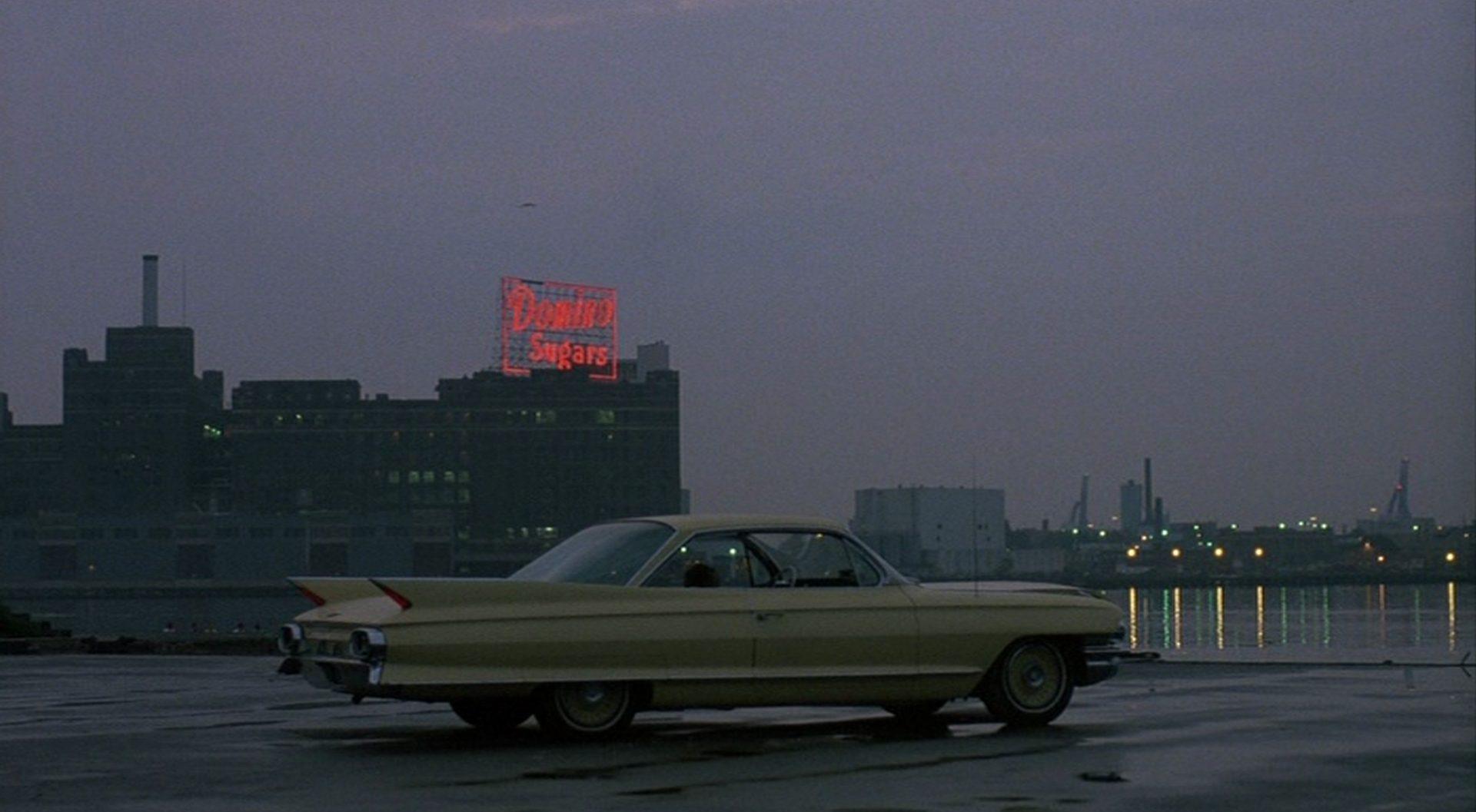 Limousine mit spitzen Heckflossen in der Dämmerung am Pier, im Hintergrund Hafenlichter.