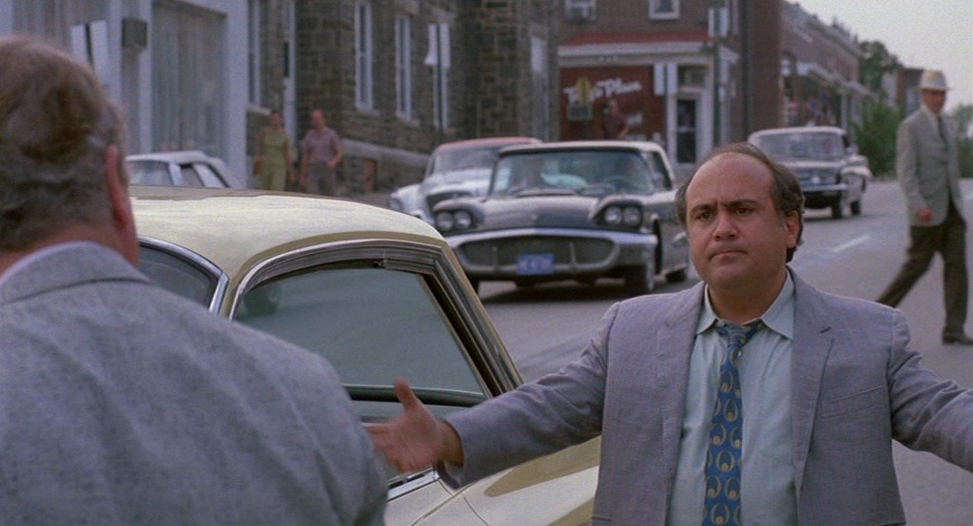 Danny DeVito als Ernest Tilley mit ernster Miene am Straßenrand.