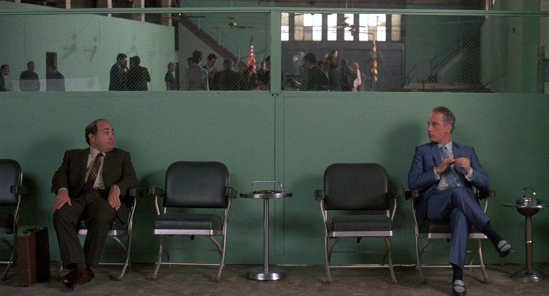 Danny DeVito und Richard Dreyfuss als die beiden Vertreter Ernest Tilley und Bill Babowsky auf gegenüberliegenden Seiten einer Stuhlreihe in einem Warteraum, die Blicke einander zugerichtet.