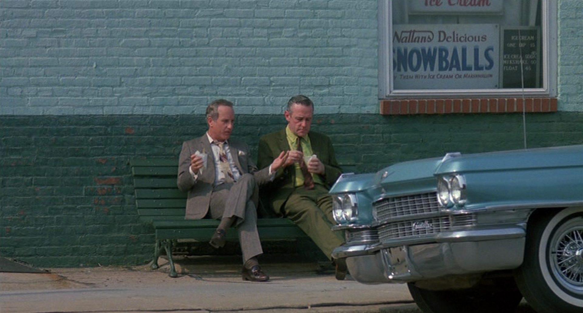 Babowsky und Moe Adams unterhalten sich auf einer Bank vor einer Mauer, im Vordergrund die Front einer chromlastigen Limousine.