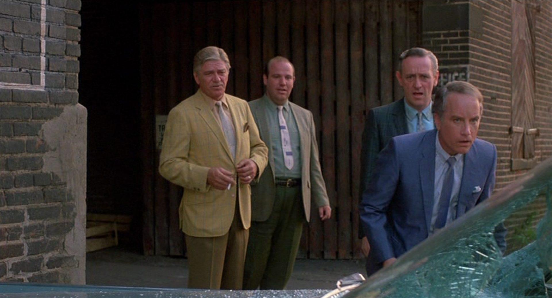 Richard Dreyfuss als Bill Babowsky betrachtet im Beisein von Kollegen in verwunderter Ärgerlichkeit eine zertrümmerte Windschutzscheibe.