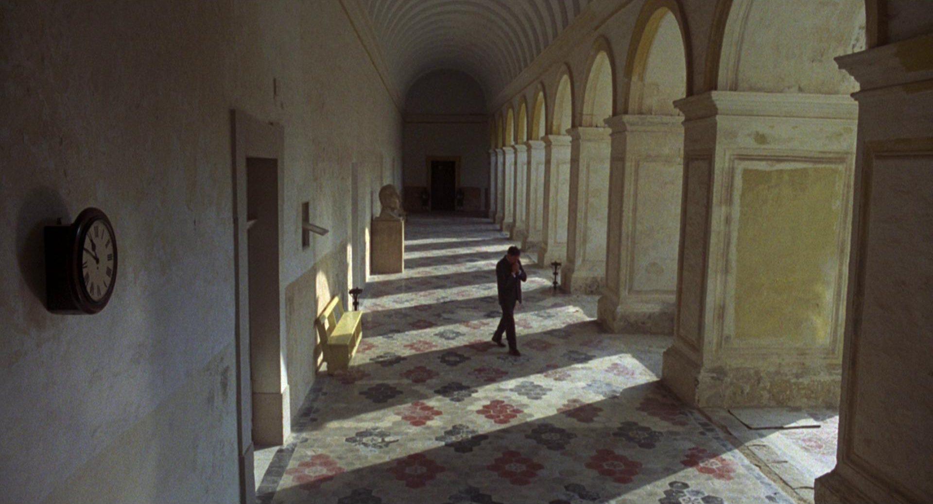 Ein Mann schreitet in nervöser Pose den Portikus eines alten, monumentalen Gebäudes entlang.