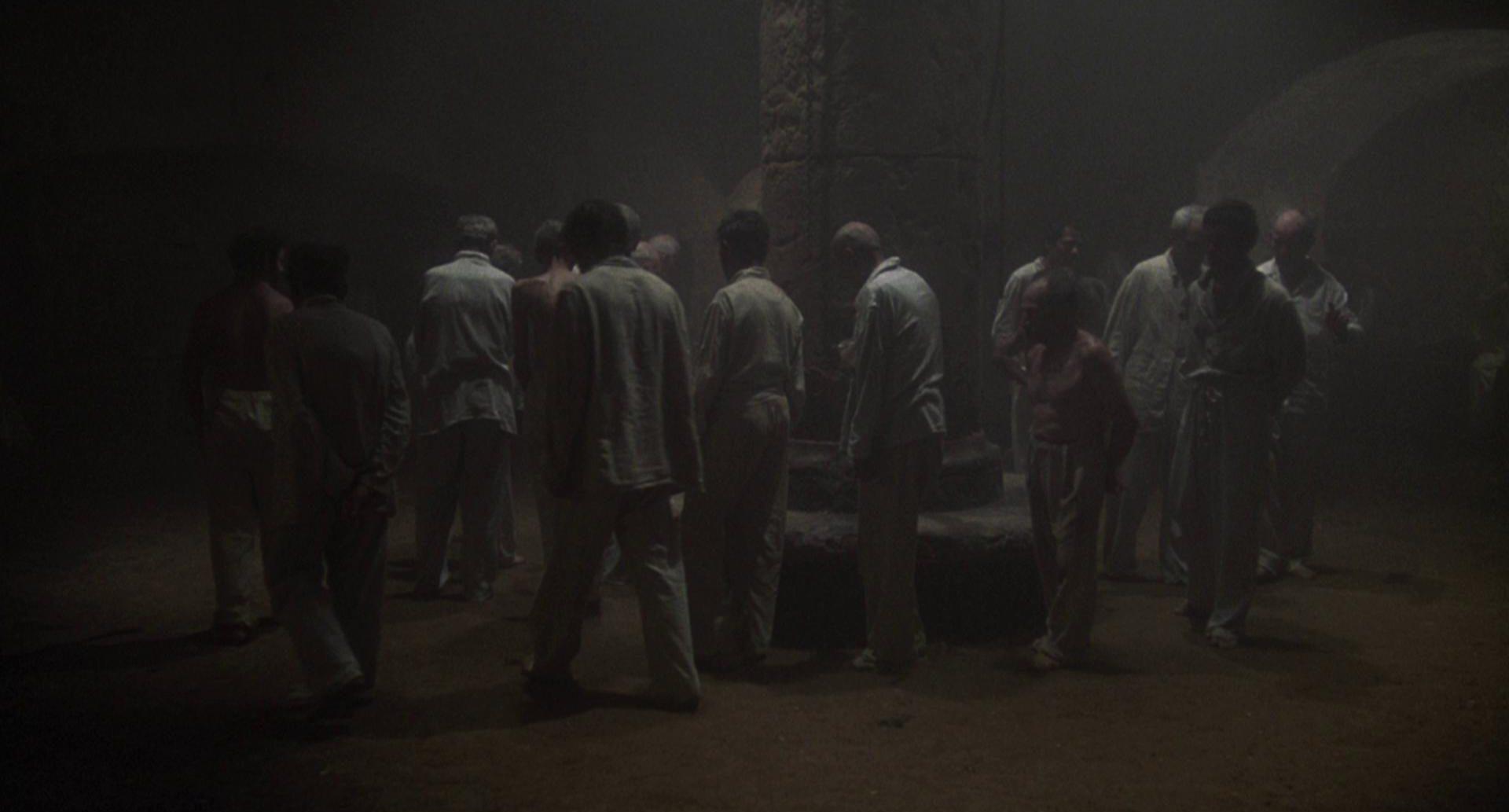 Häftlinge bewegen sich im Kreisgang durch einen düsteren Raum.