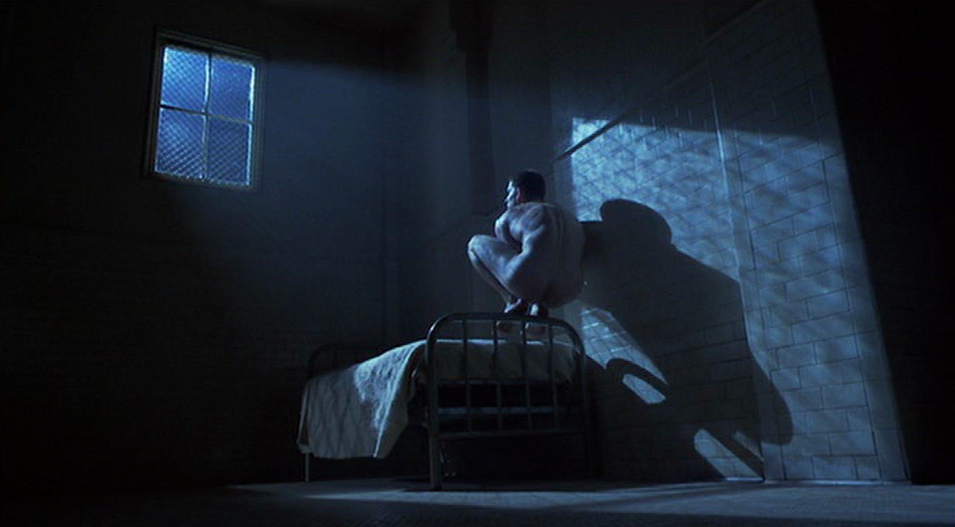 Matthew Modine kauert nackt als Birdy auf der Kante des Bettgestells im Mondschein, der durch das Fenster eines dunklen Psychiatriezimmers dringt.