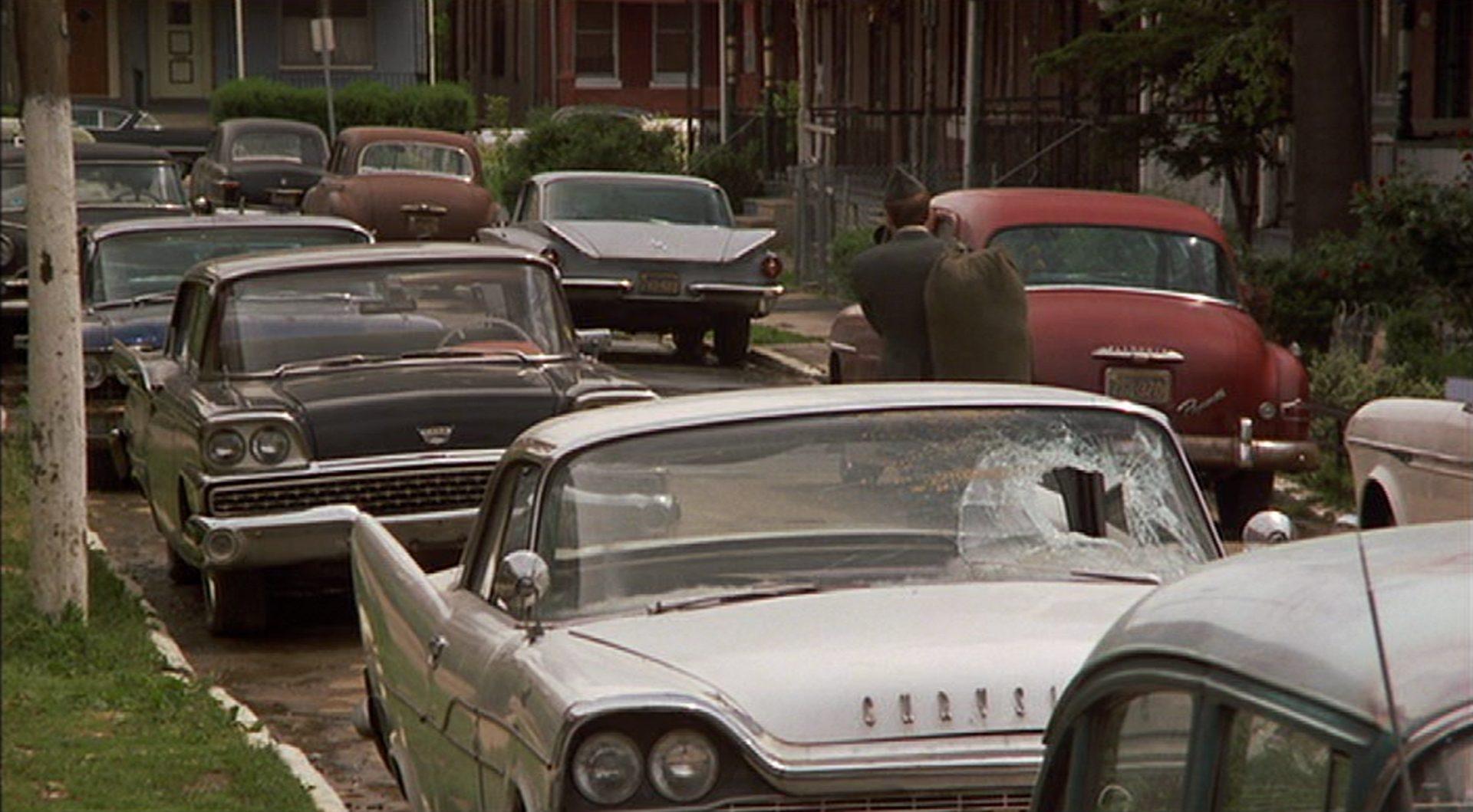 Blick durch eine Slum-Straße in Philadelphia; viele geparkte Limousinen verströmen das Zeitkolorit der 1960er Jahre.