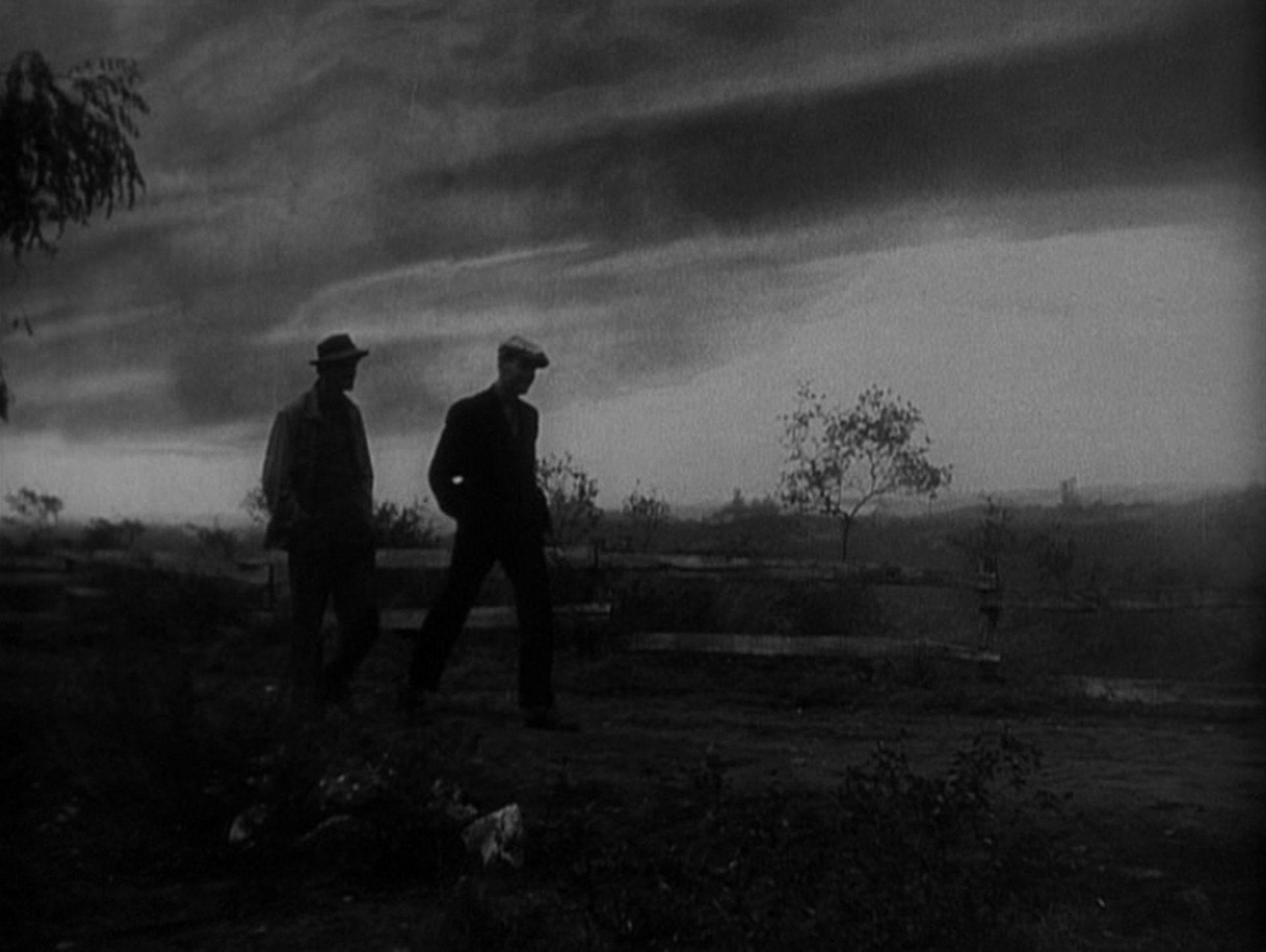 Zwei Männer durchschreiten in der Dämmerung eine triste Umgebung.