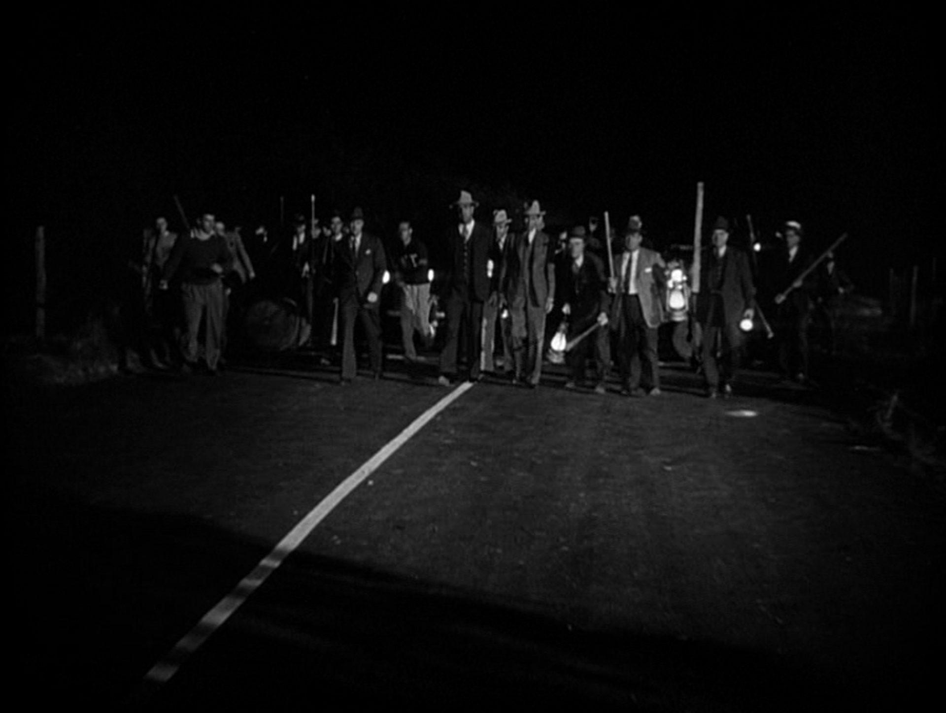 Eine Straßensperre mit bewaffneten Männern in der Nacht.