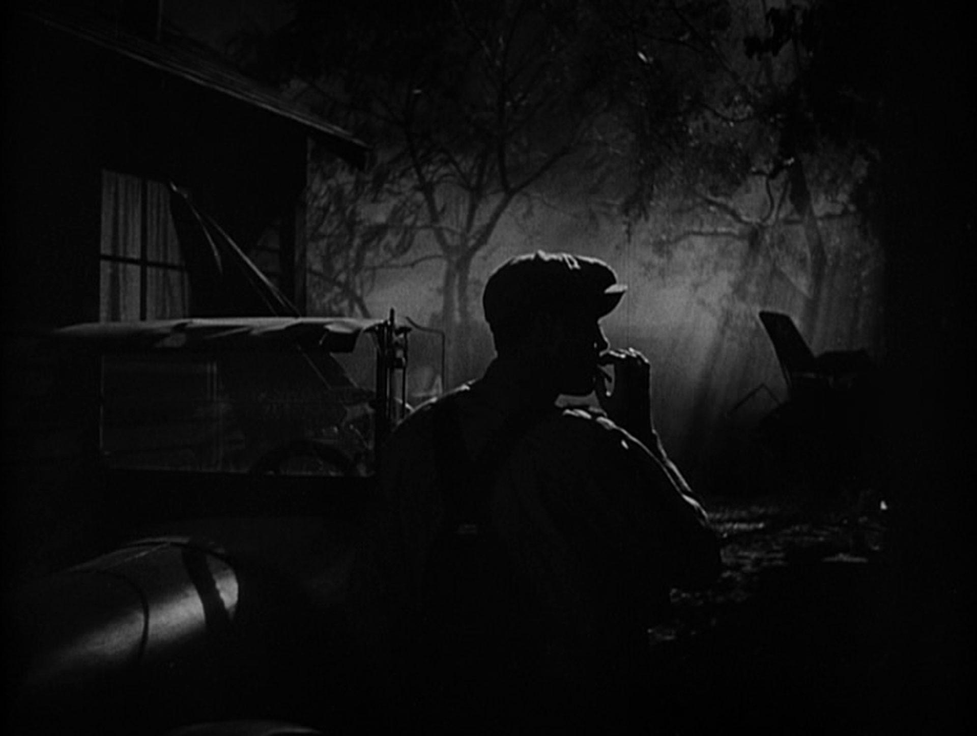 Tom Joad in der Nacht, wie er an einer Zigarette zieht.