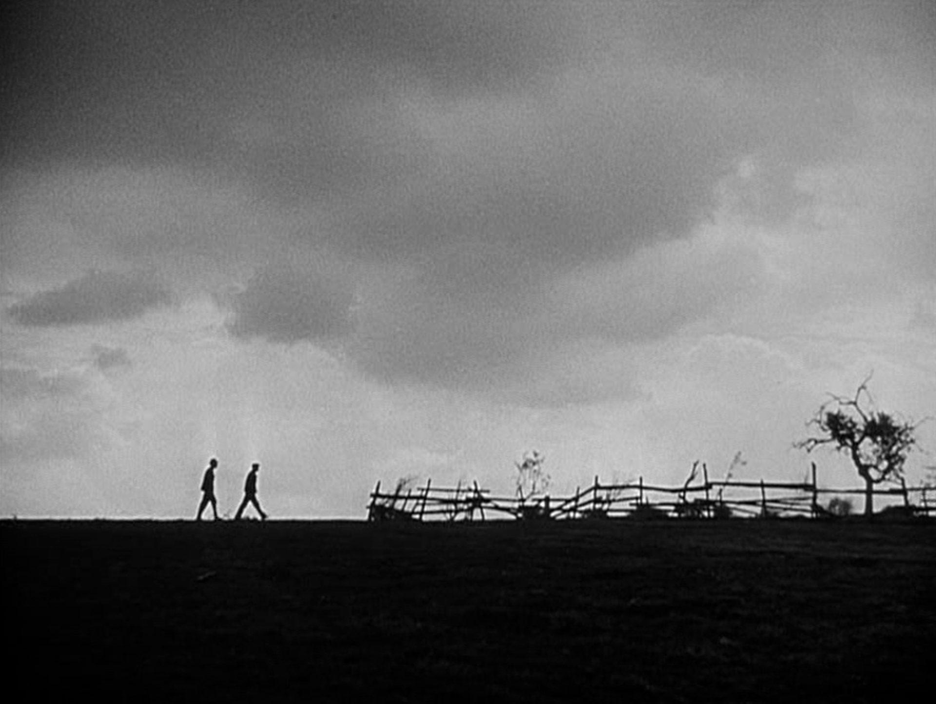 Zwei Männer zeichnen sich als Silhouetten am Horizont einer finsteren Landschaft ab.