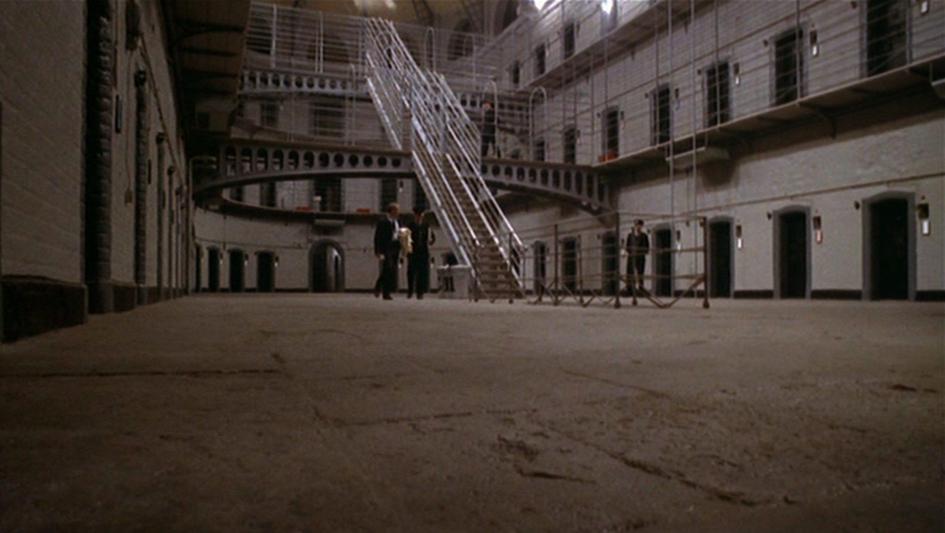 Froschperspektivischer Blick in einen großen Gefängnistrakt.