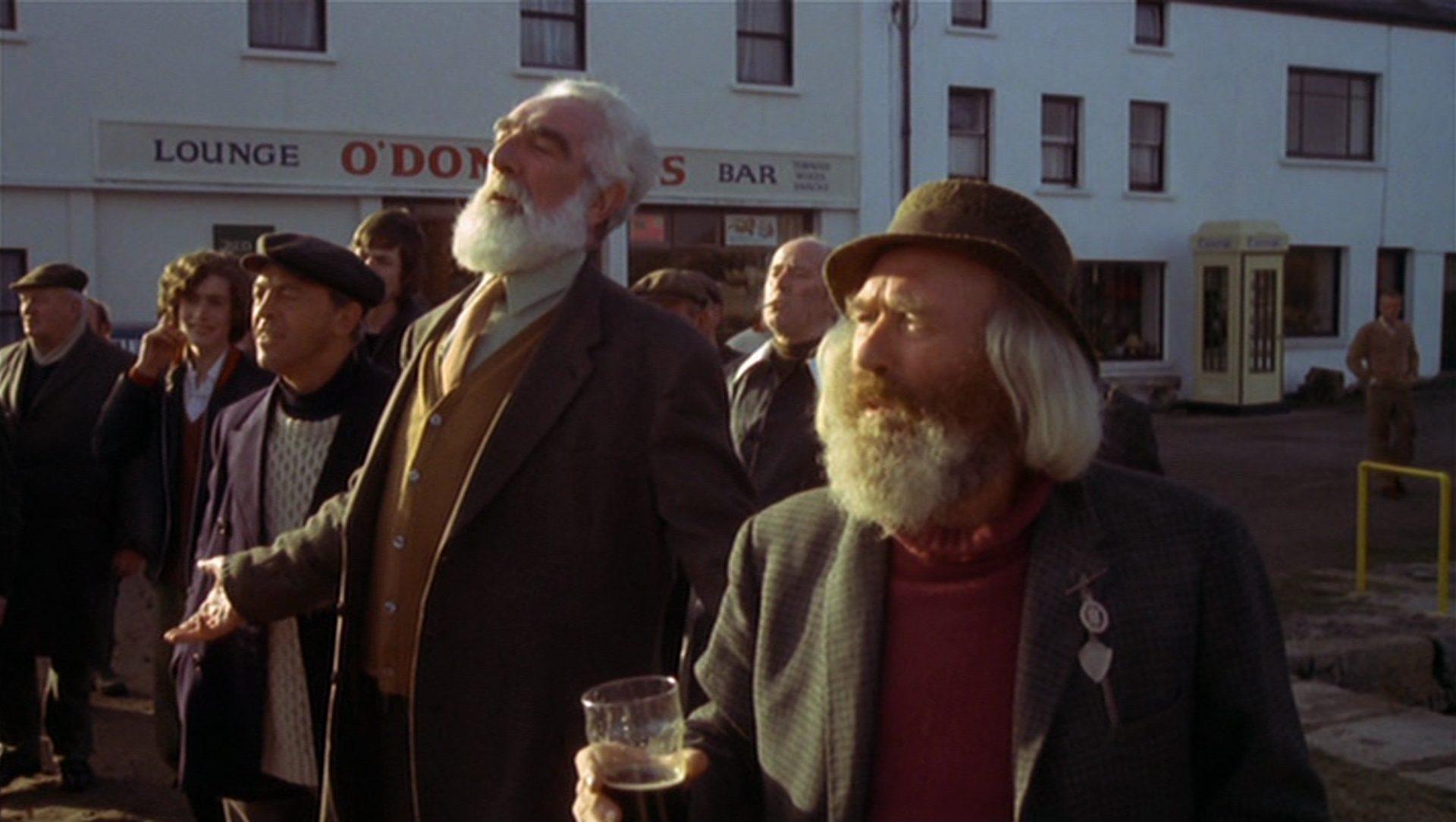 Eine Gruppe größtenteils älterer Dorfbewohner blicken auf etwas außerhalb des Bildausschnitts.