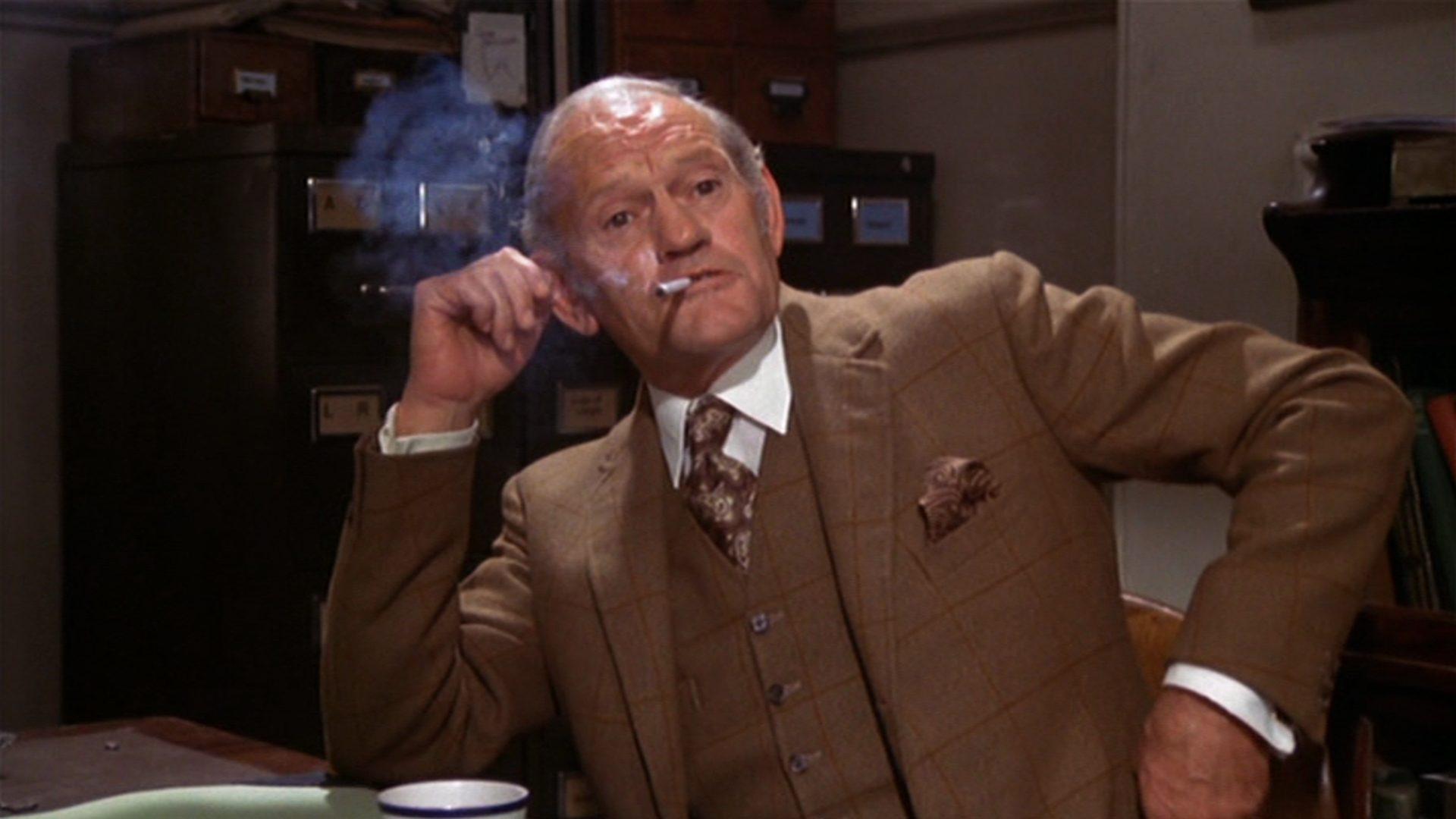 Nahaufnahme von Harry Andrews als Geheimdienstler Mackintosh mit Zigarette in einem Büro.