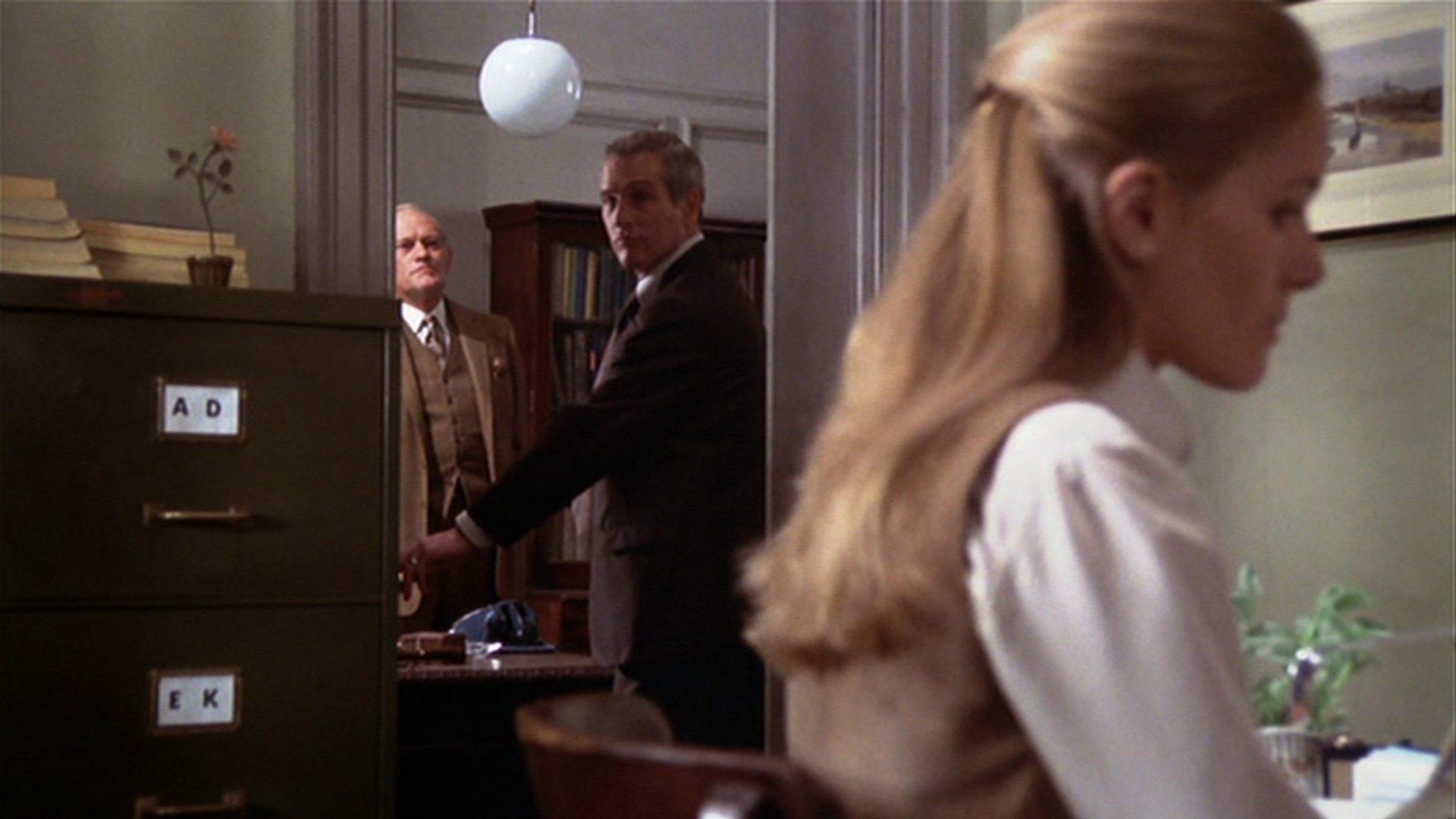 Im Hintergrund Harry Andrews und Paul Newman, im Vordergrund Dominique Sanda in einem Büro.