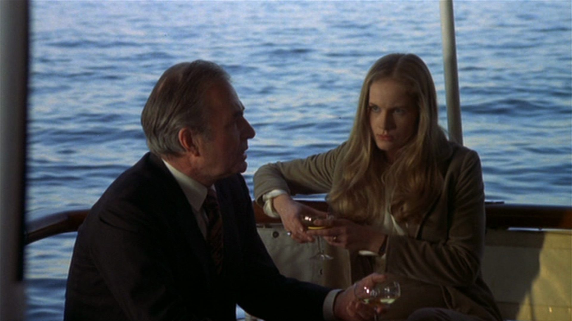 James Mason als Wheeler beim gemeinsamen Drink mit Mrs. Smith, gespielt von Dominique Sanda, auf Wheelers Jacht.