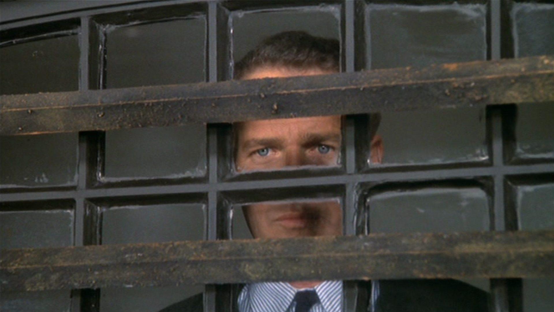 Nahaufnahme von Paul Newman beim Blick aus einem vergitterten Fenster.