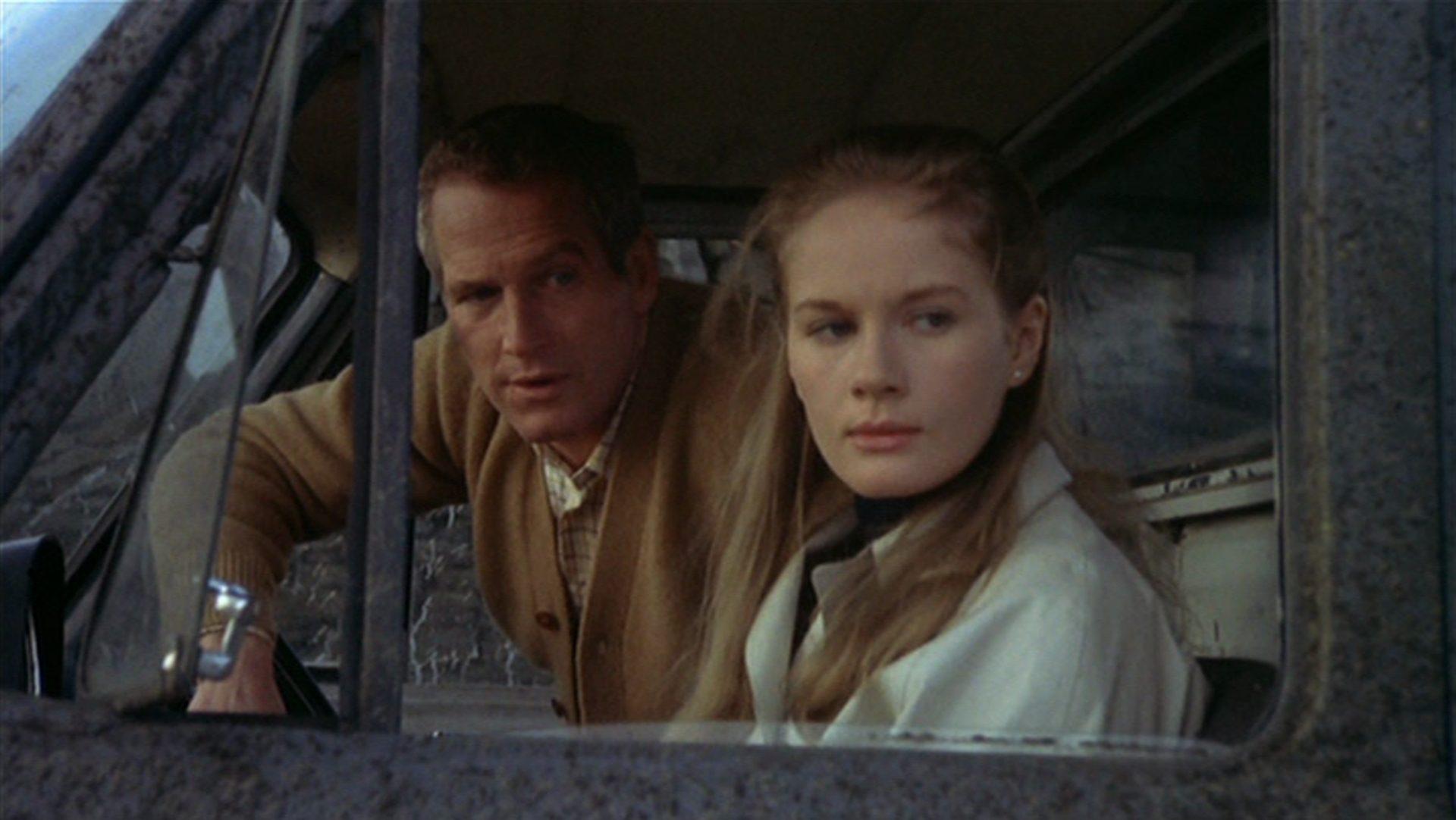 Nahaufnahme von Paul Newman und Dominique Sanda als Reardon und Smith beim Blick aus einem geöffneten Fahrzeugfenster.