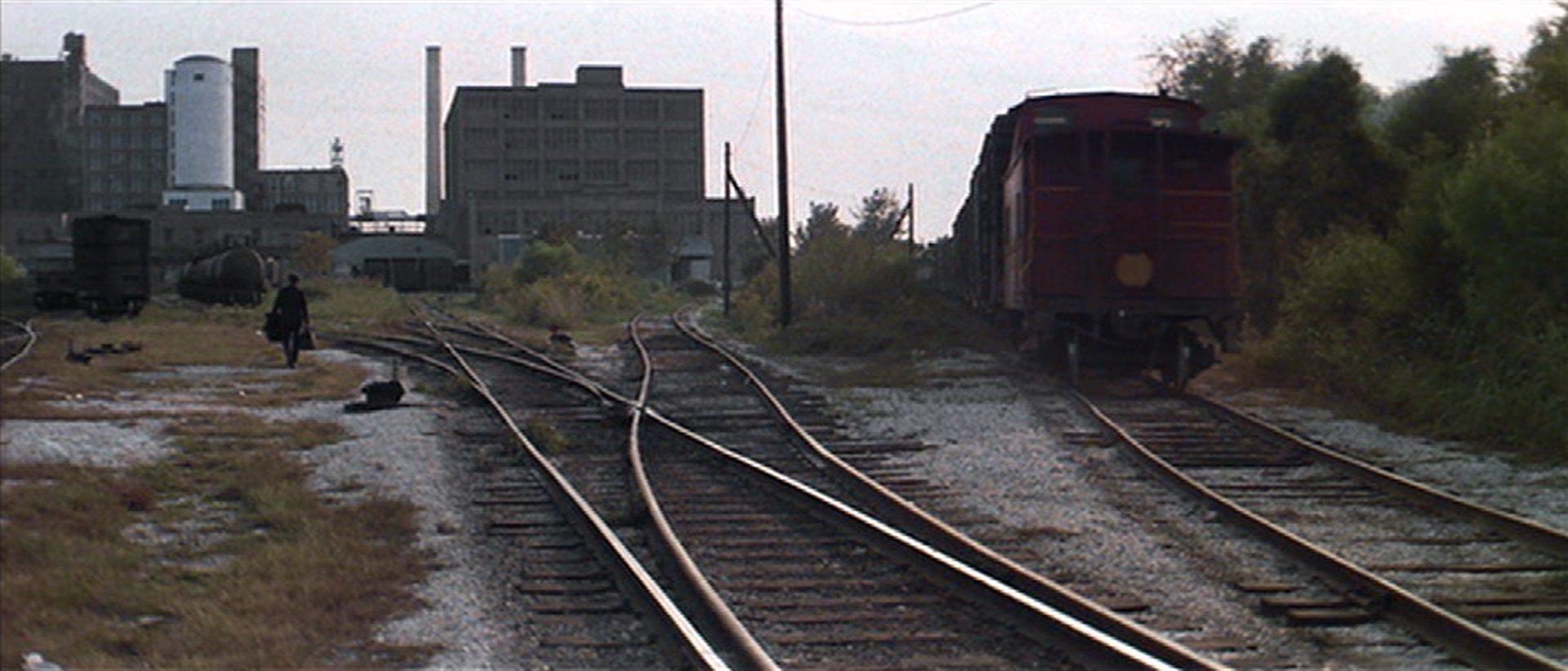 Eisenbahngleise mit industriellem Hintergrund, links im Bild geht ein Drifter.