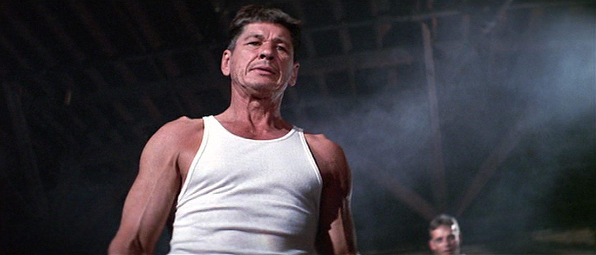 Charles Bronson mit muskulösem Oberkörper im weißen Unterhemd aus der Froschperspektive.