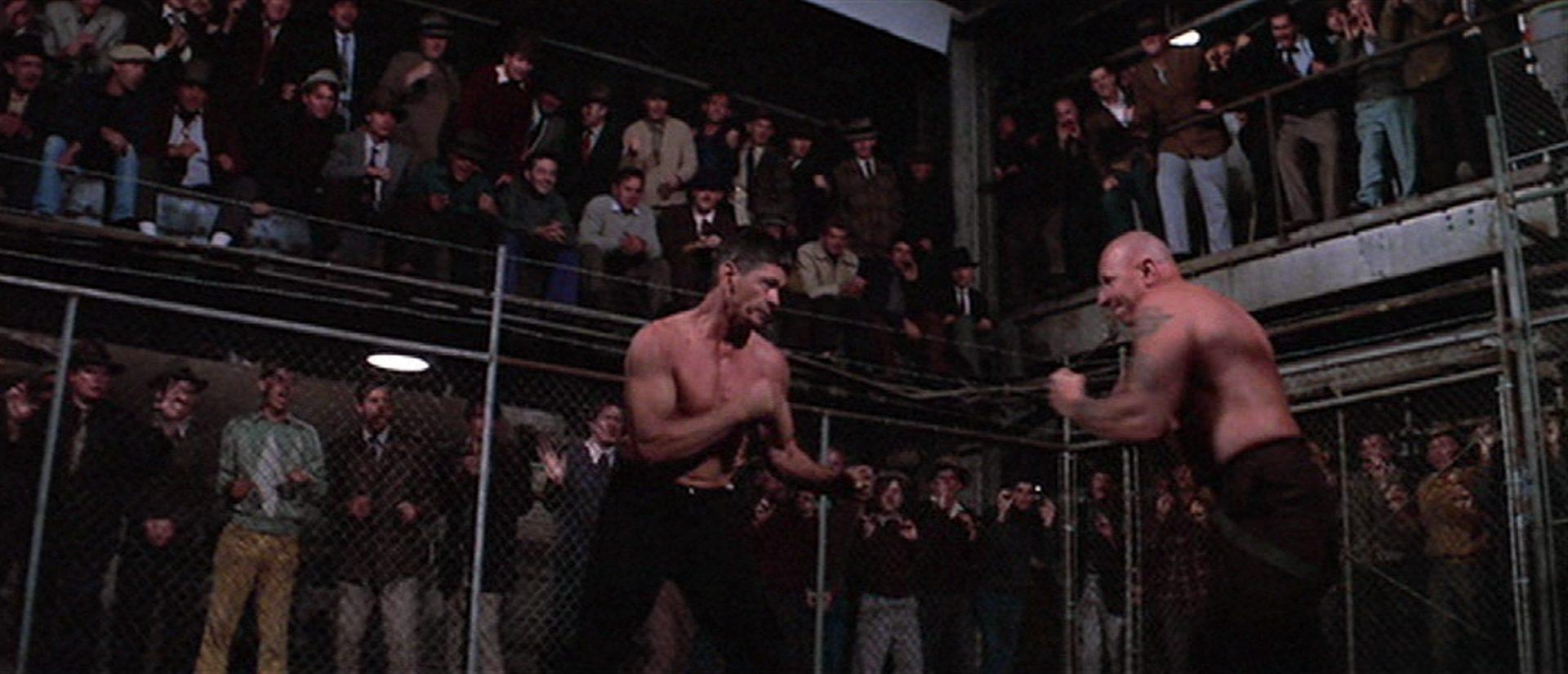 Charles Bronson als Streetfighter in Zweikampfpose in einer hitzigen Arena vor Publikum mit einem von Robert Tessier gespielten Gegner.