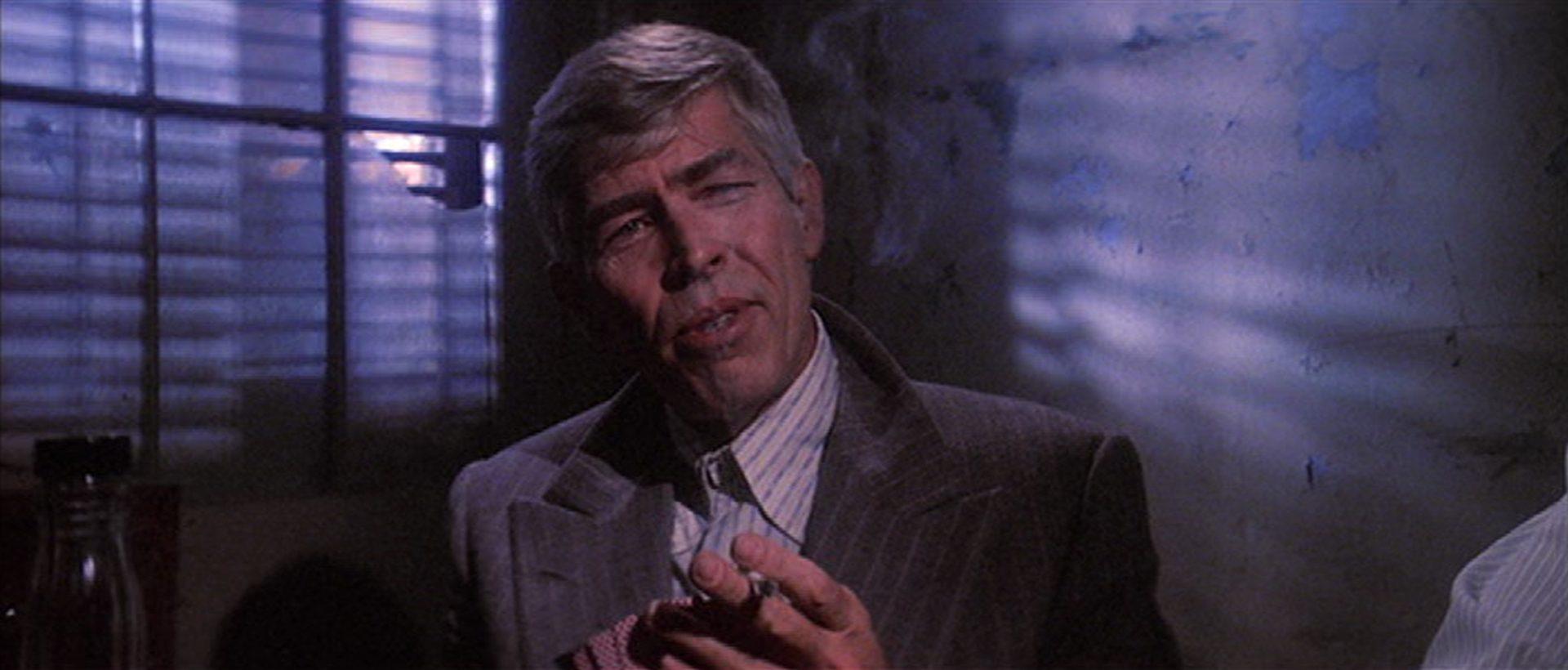 Nahaufnahme von James Coburn in der Pose eines windigen Geschäftsmannes.