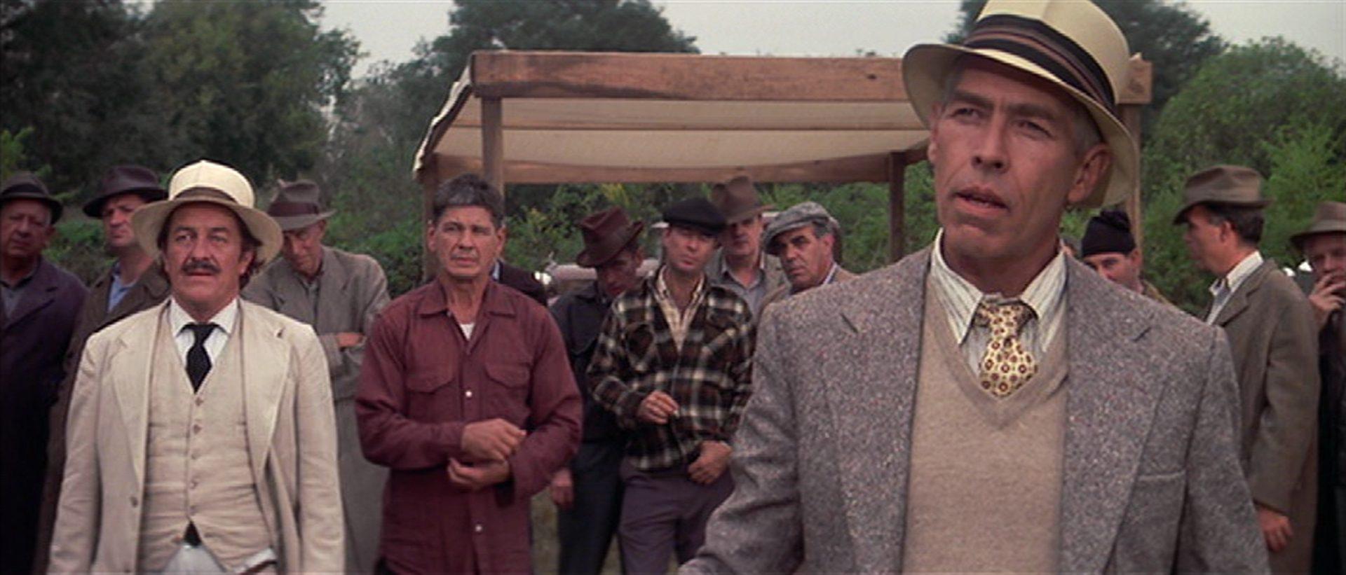 Im Vordergrund James Coburn in selbstbewusster Pose als Speed, im Hintergrund Strother Martin als Arzt und Charles Bronson als Faustkämpfer in skeptischer Warteposition.