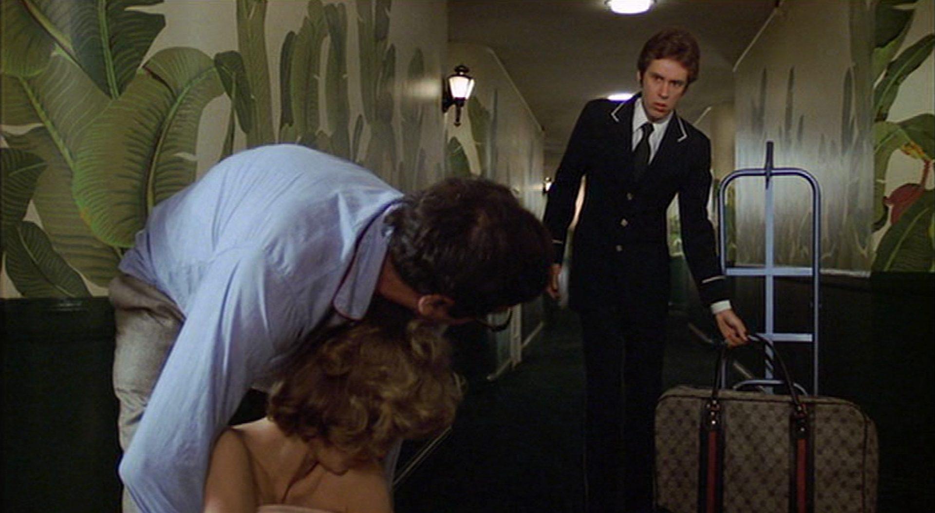 Irritierter Blick eines Hotelangestellten auf Matthau, der gerade die schlafende Frau auf den Etagenflur zerrt.