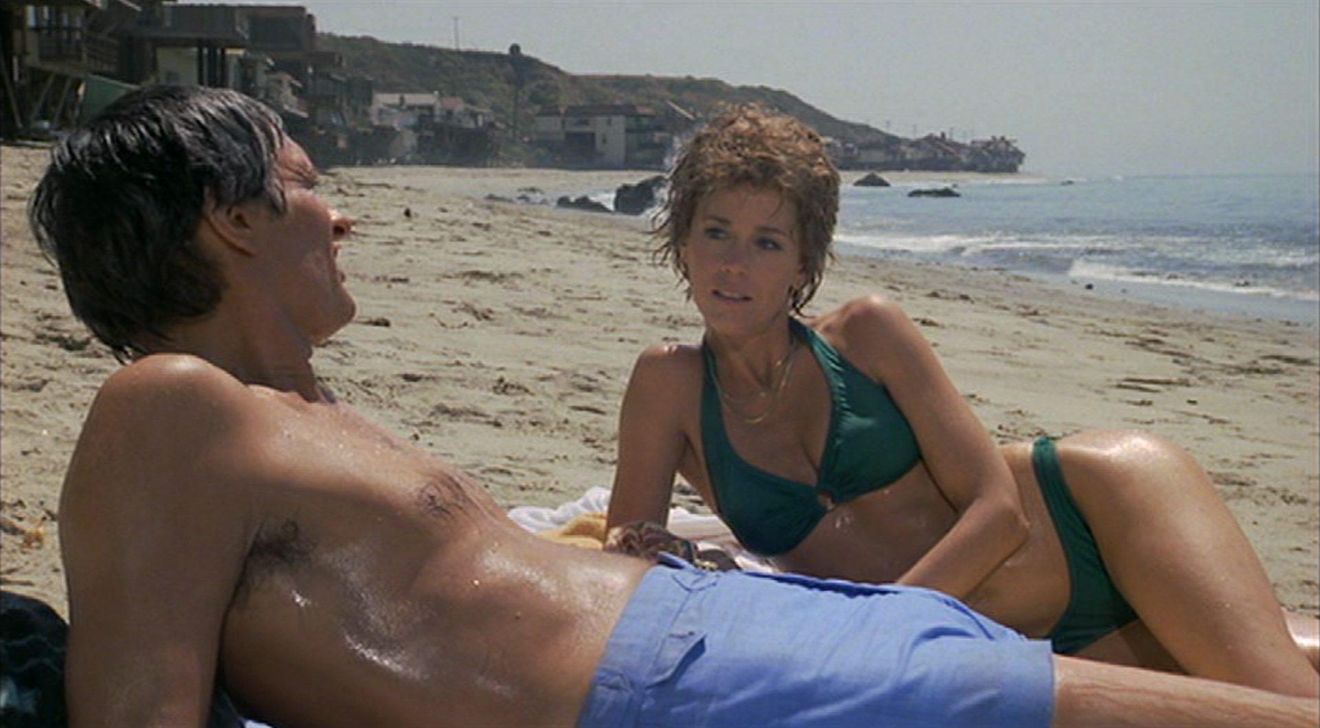 Alan Alda und Jane Fonda liegen in sonniger BEkleidung am Strand.