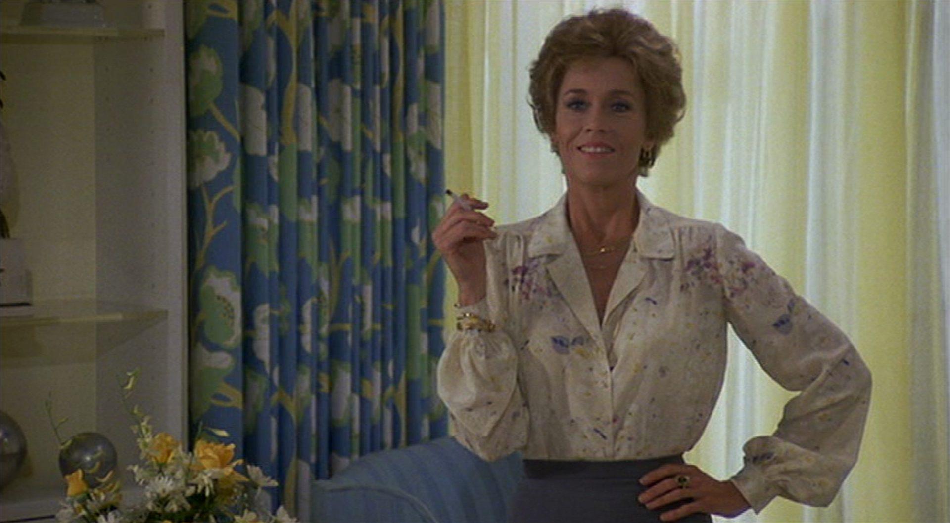 Nahaufnahme von Jane Fonda mit Zigarette im Hotelzimmer, das voll entsättigtem Seventies-Flair ist.