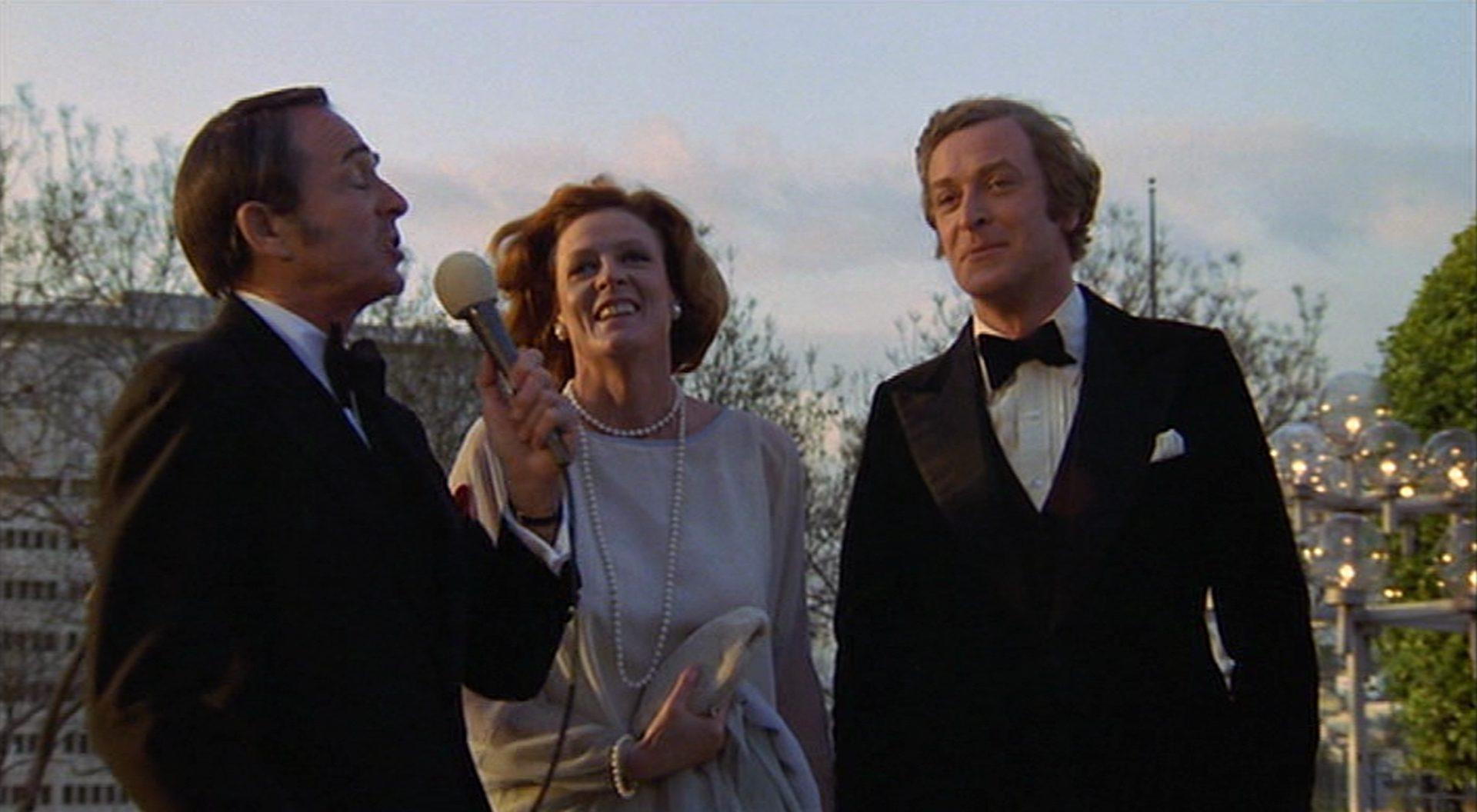 Maggie Smith und Michael Caine in festlichem Outfit begegnen einem Interviewer mit angestrengtem Lächeln.