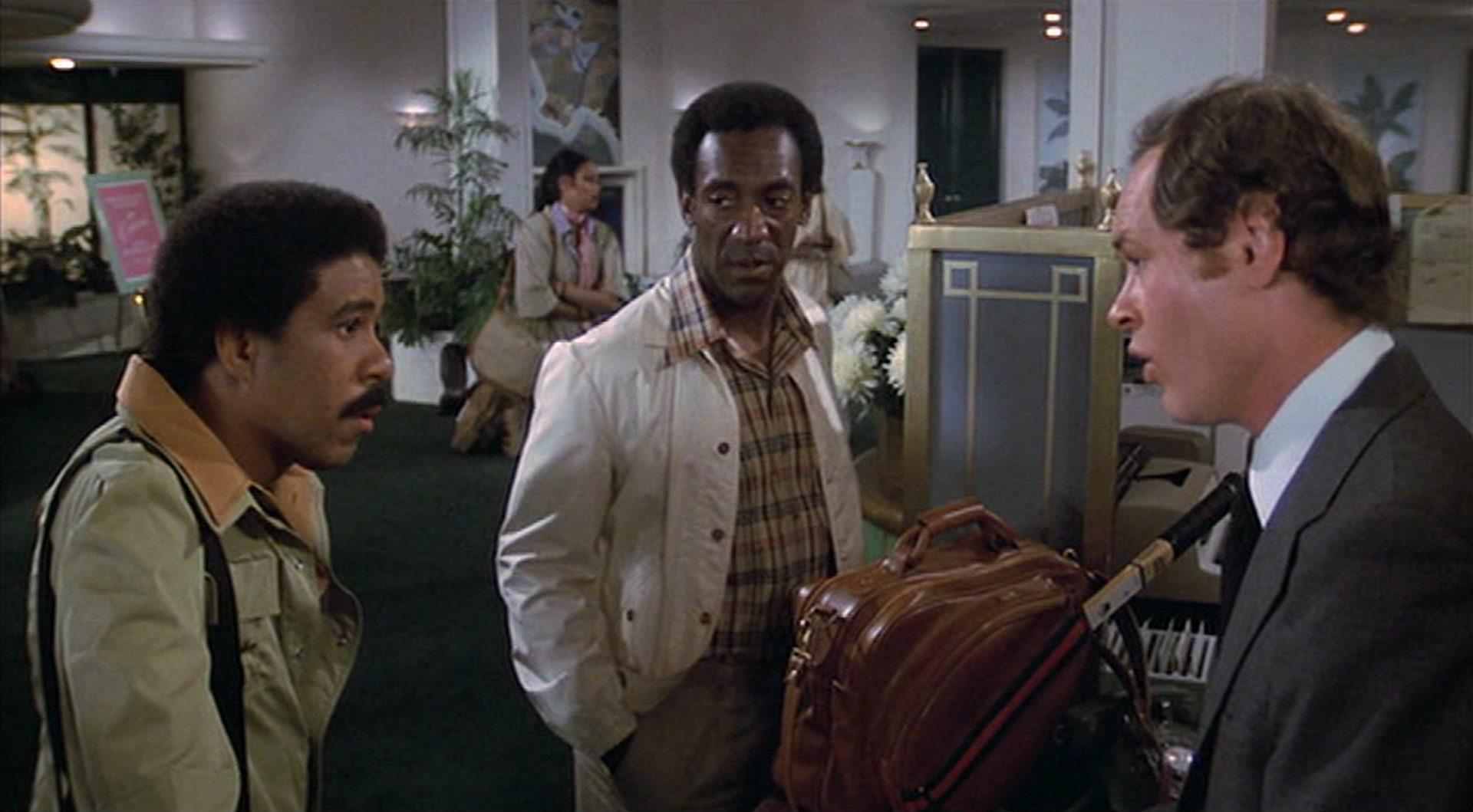 Richard Pryor und Bill Cosby in strapazierter Haltung im Hotelfoyer im Gespräch mit dem Rezeptionisten.
